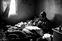 Punchie huddled under blankets in an abandoned West Garfield Park home-1910