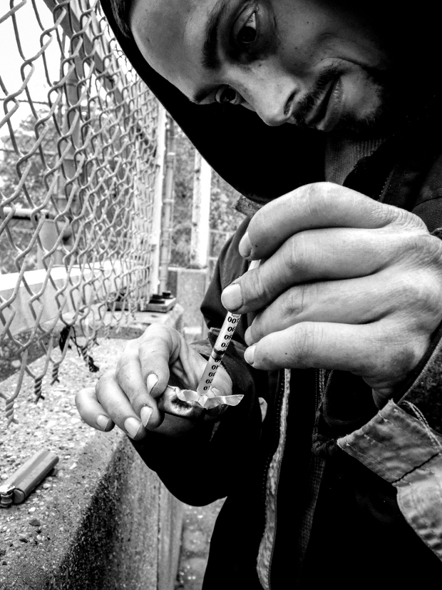 John Lee draws heroin into his syringe while standing on an overpass above the Eisenhower Expressway in Chicago, October 15, 2014