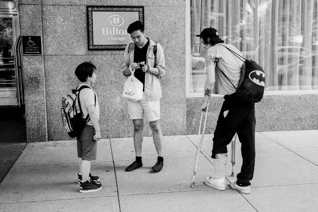 A man searches through his wallet for a single dollar bill to give to Shaggy outside the Chicago Hilton Hotel.