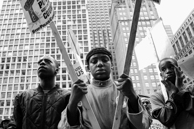 CHICAGO, IL. Aug. 29, 2015 - Young men hold signs in Chicago's Daley Plaza during a political protest against police brutality.