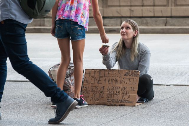 CHICAGO, IL. Sep 6, 2015 - A young girl gives heroin addict, Mandrell White, age 34, a donation while on Chicago's Michigan Ave.