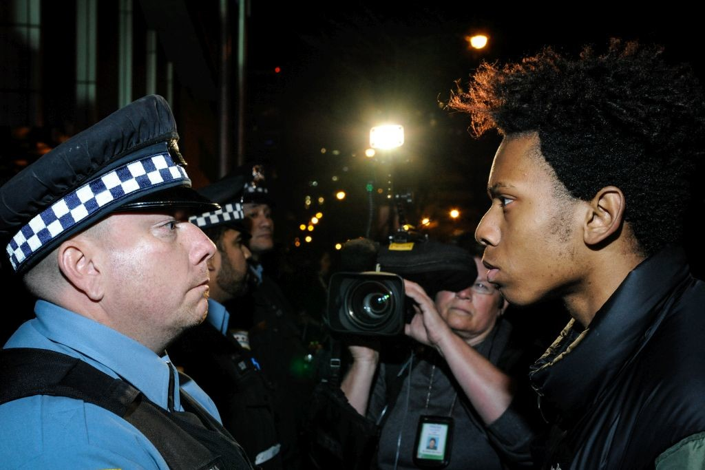 """""""I want you to beat me with that stick"""" says a protester as he attempts to provoke a Chicago Police Officer during a protest Tuesday evening of the shooting death of 17-year-old Laquan McDonald in October 2014."""