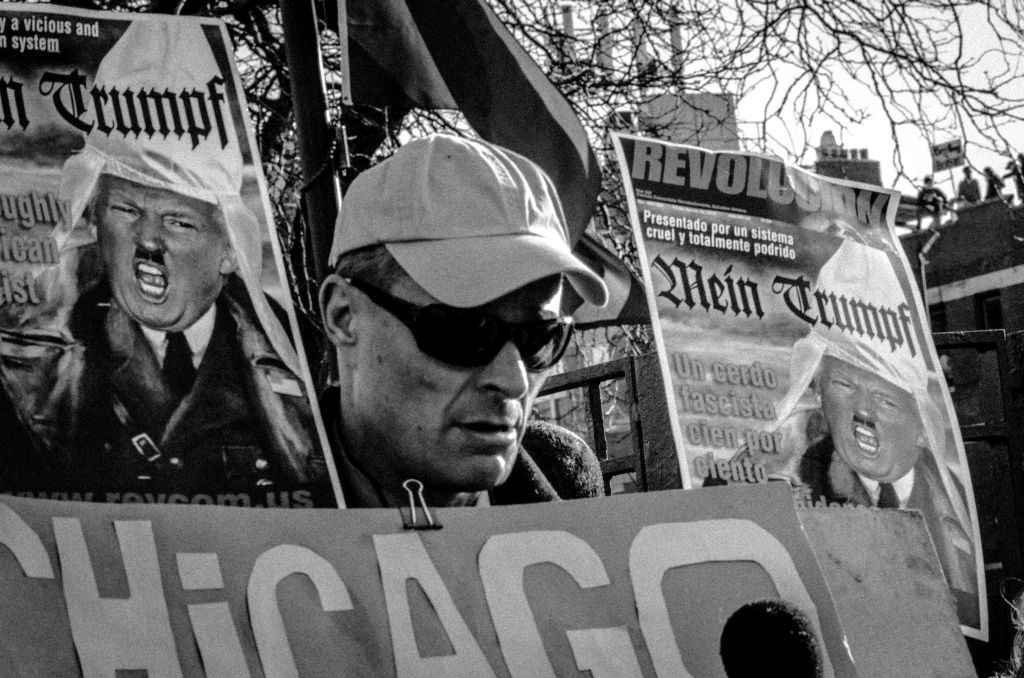 A protester being interviewed by Channel 5 News outside a Trump rally in Chicago. The signs in the background depicting Trum as a Nazi, were made by a local Bob Avakian Communist group that actually encourages blacks to take up arms. Avakian is the Chairman of the Revolutionary Communist Party, USA.